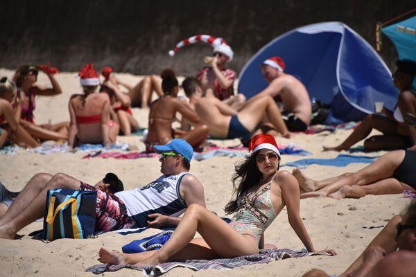 Турист в рождественской шапке на пляже Бонди в Сиднее