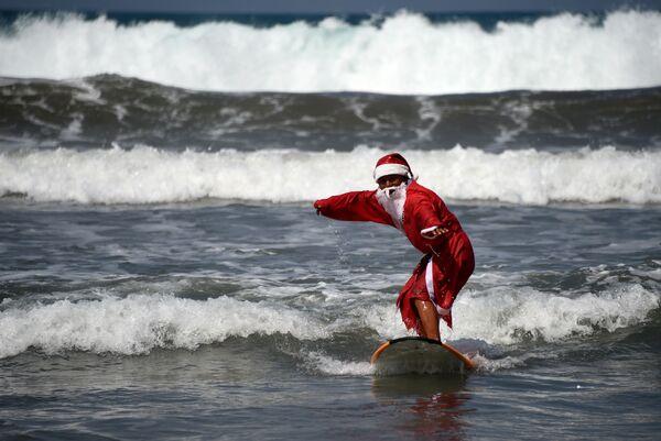 Серфер, одетый в костюм Санта-Клауса на пляже Кута на острове Бали