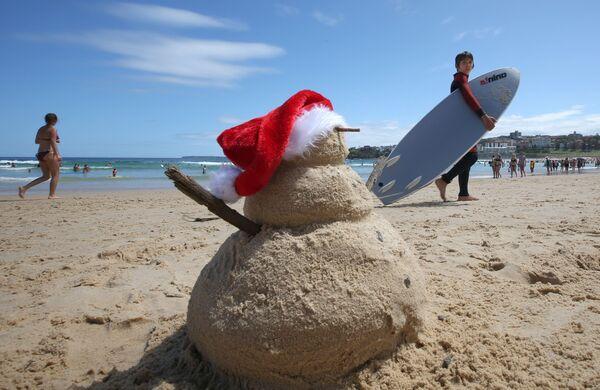 Снеговик из песка в шапке Санта Клауса на пляже в Сиднее, Австралия