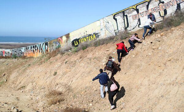 Мигранты из каравана беженцев пытаются нелегально пересечь границу в Тихуане, Мексика