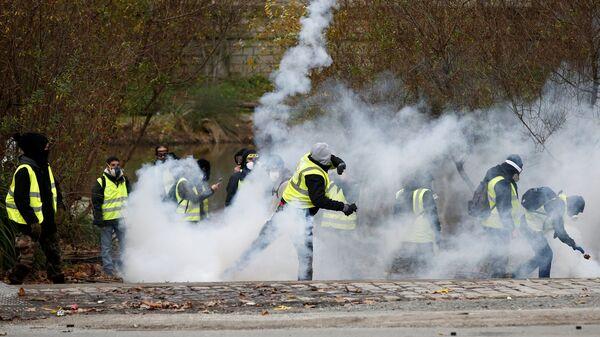 Участники акции протеста желтые жилеты во время столкновения с полицией в Париже