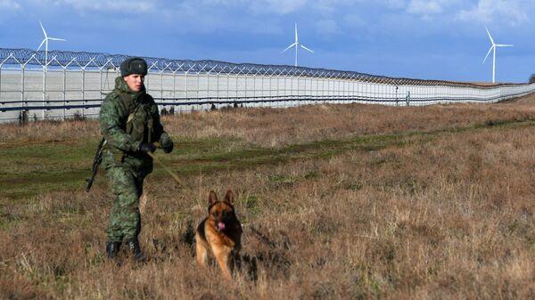 Российский пограничник со служебной собакой у заграждения, возведенного в Крыму на границе с Украиной