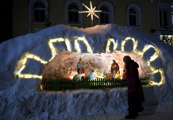 Верующая у вертепа во время рождественского богослужения