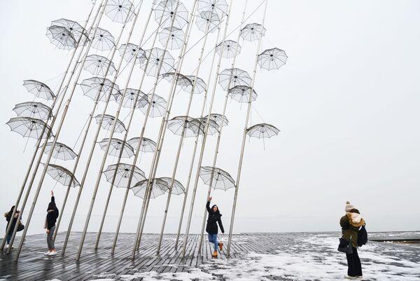 Девушки фотографируются на фоне инсталляции Зонтики на набережной в Салониках
