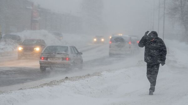 Прохожий на одной из улиц во время снегопада