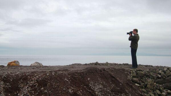 Председатель правительства России Дмитрий Медведев фотографирует остров Итуруп