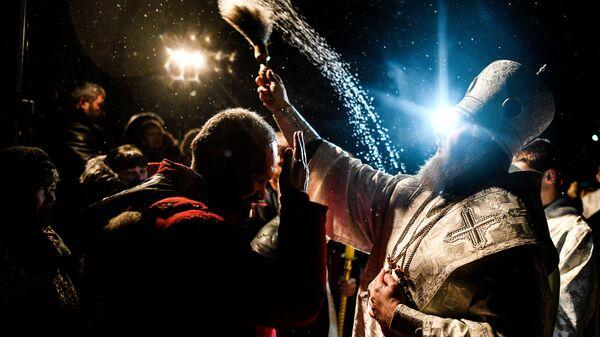 Священник окропляет святой водой присутствующих во время традиционных купаний в праздник Крещения у церкви Сорока Мучеников Севастийских в Переславле-Залесском. 19 января 2019