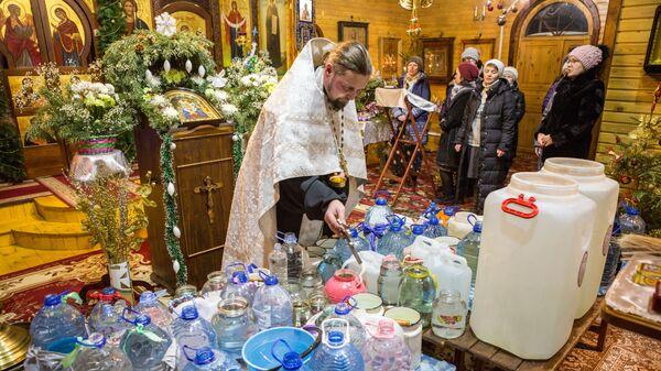 Настоятель храма, иерей Константин Кукушкин совершает чин освящения воды во время крещенской службы в Храме Покрова Пресвятой Богородицы в поселке Пряжа