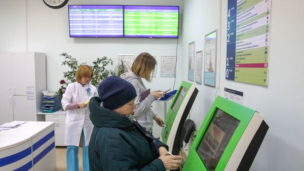 Пациенты записываются на прием к врачу через электронные терминалы в городской поликлинике № 68 в Москве