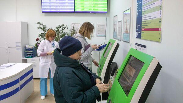 Пациенты записываются на прием к врачу через электронные терминалы в московской поликлинике