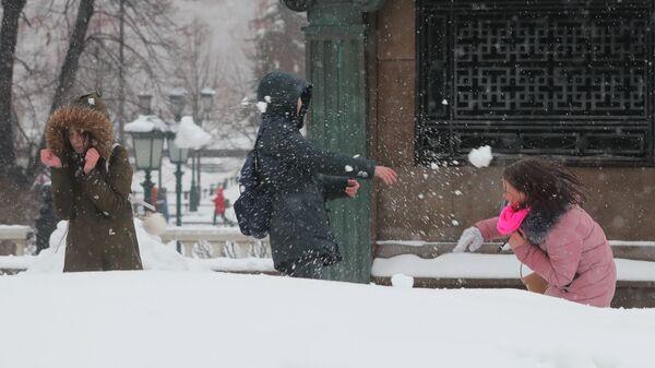 Молодые люди играют в снежки на Манежной площади в Москве
