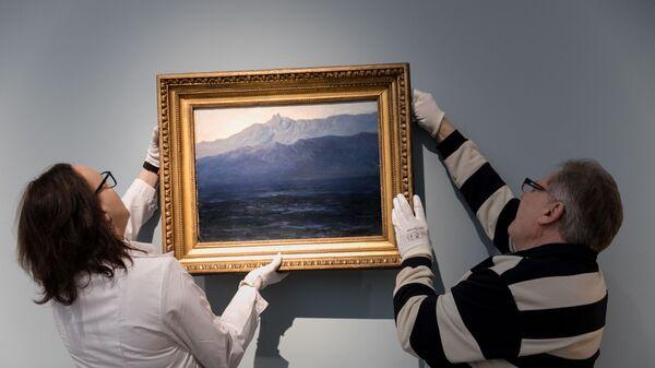 Сотрудники Третьяковской галереи в Москве вешают на стену картину Архипа Куинджи Ай-Петри. Крым