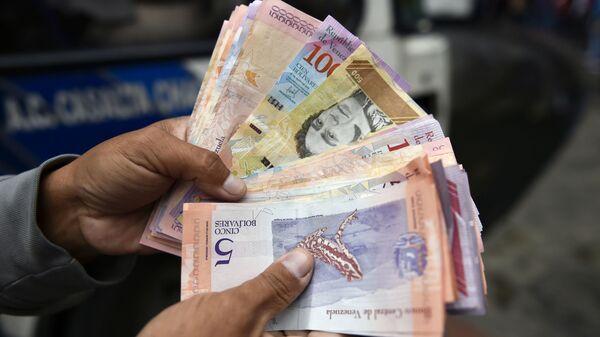Мужчина пересчитывает деньги на улице в Каракасе