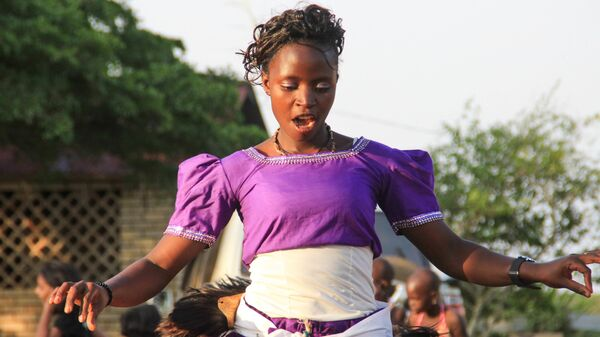 Африканская певица выступает на уличном мероприятии в Кампале, Уганда