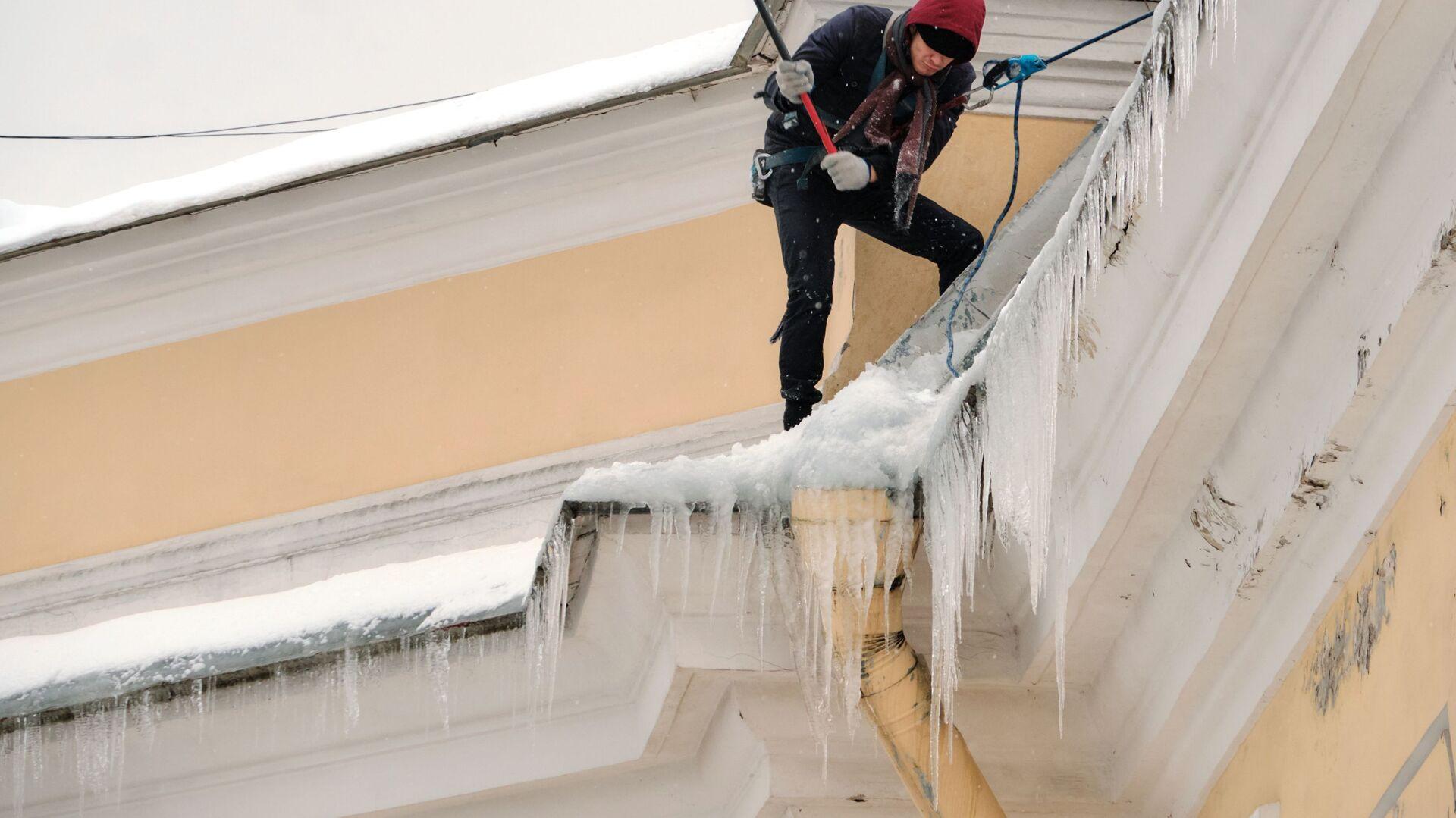 Работник коммунальной службы чистит от снега и сосулек крышу дома в Санкт-Петербурге - РИА Новости, 1920, 23.01.2021