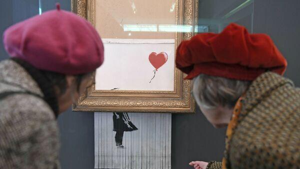 Посетители рассматривают самоуничтожившуюся картину Бэнкси Любовь в мусорной корзине в музее Фридера Бурды в Баден-Бадене
