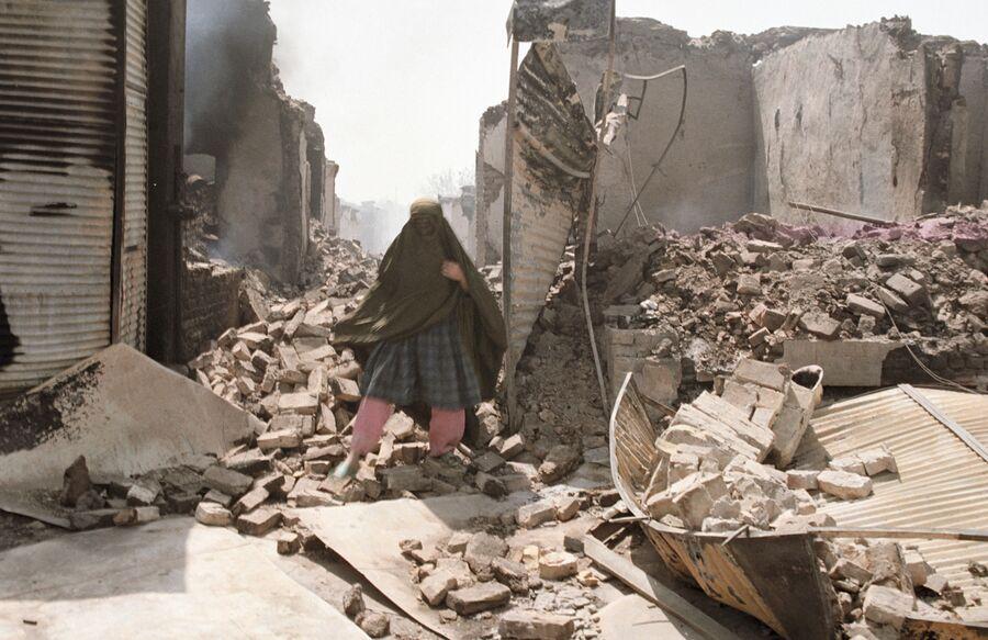 Жительница Кундуза на руинах, оставленных отрядами исламской оппозиции во главе с Ахмад Шахом Масудом