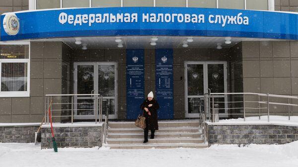Женщина выходит из здания инспекции Федеральной налоговой службы России в Новосибирске