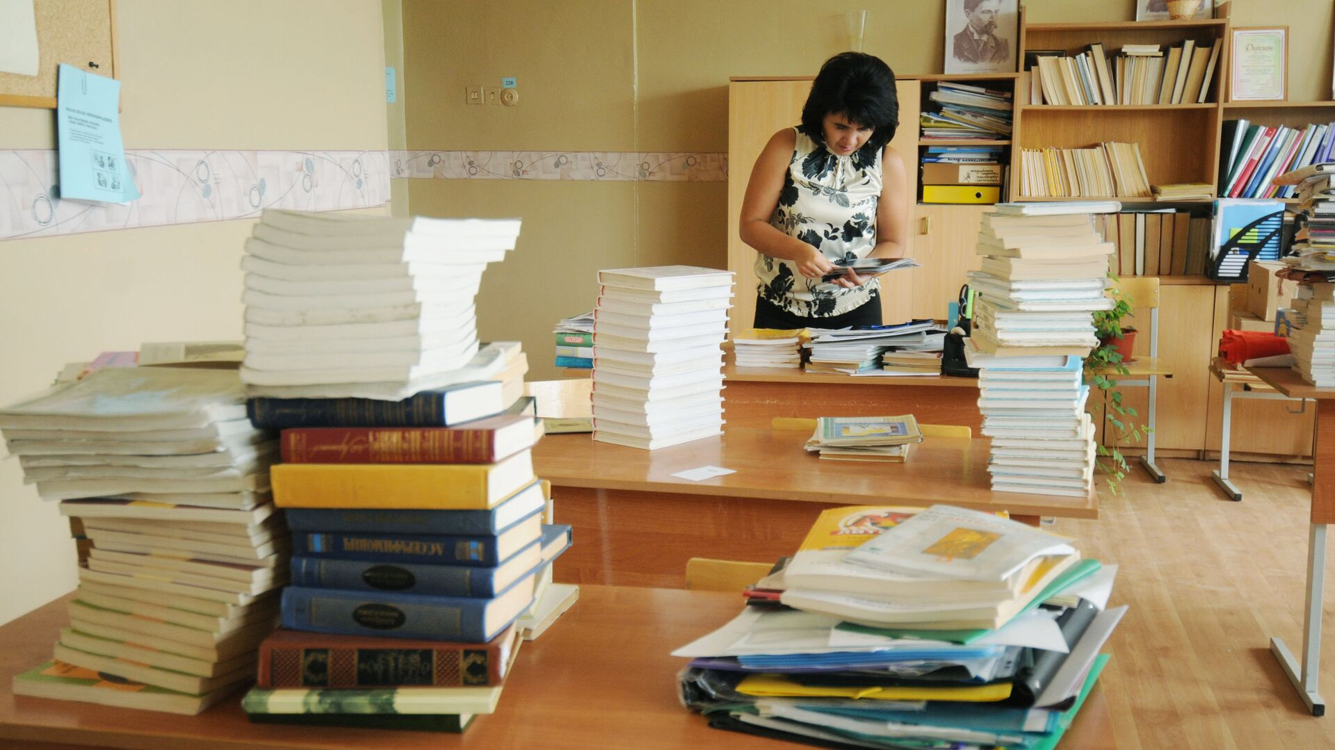 Учительница сортирует учебники в классе - РИА Новости, 1920, 07.05.2021