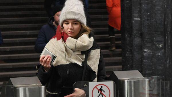 Девушка проходит через турникет на станции Курская московского метро