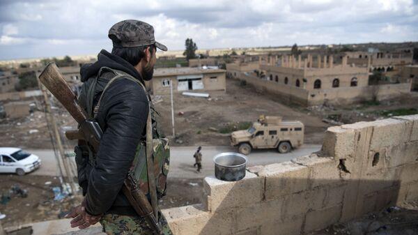 Боец Сирийских демократических сил (СДС) в деревне Багуз, Сирия