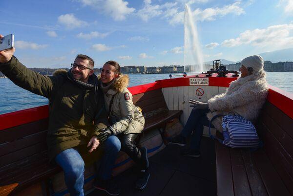 Люди фотографируются на борту прогулочного катера в Женеве