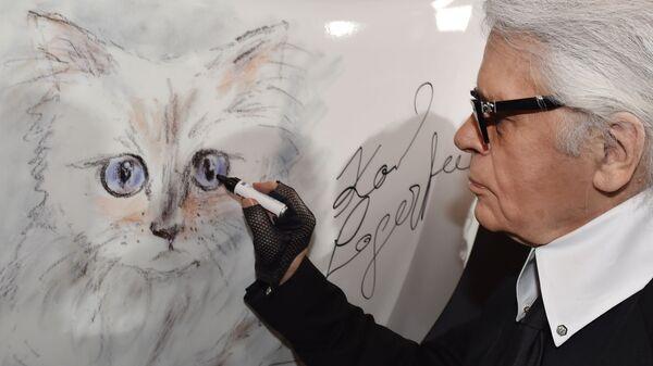 Модельер Карл Лагерфельд рядом с портретом своей кошки по кличке Шупетт