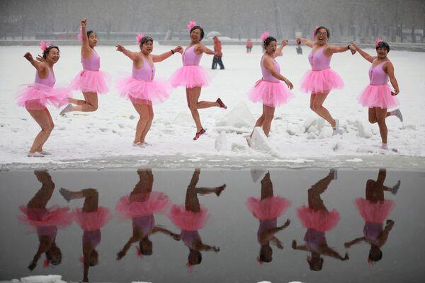 Девушки позируют перед окунанием в воду в Шеньяне, провинция Ляонин, Китай