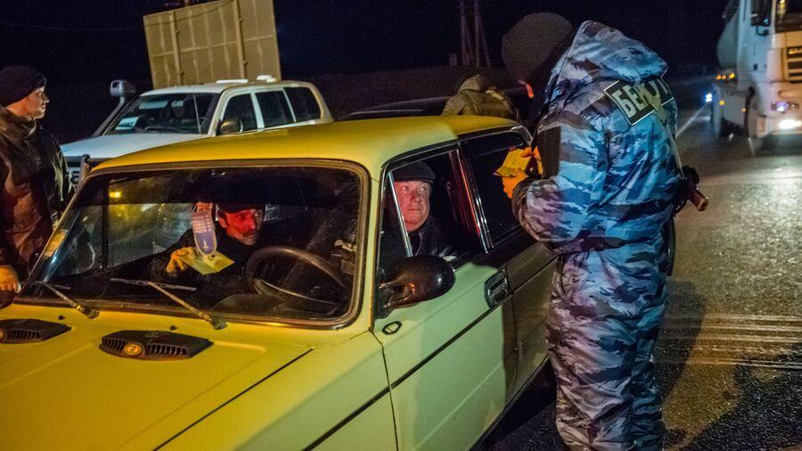Сотрудник подразделения милиции специального назначения Беркут проверяет документы на блокпосту на въезде в Крым в районе Армянска