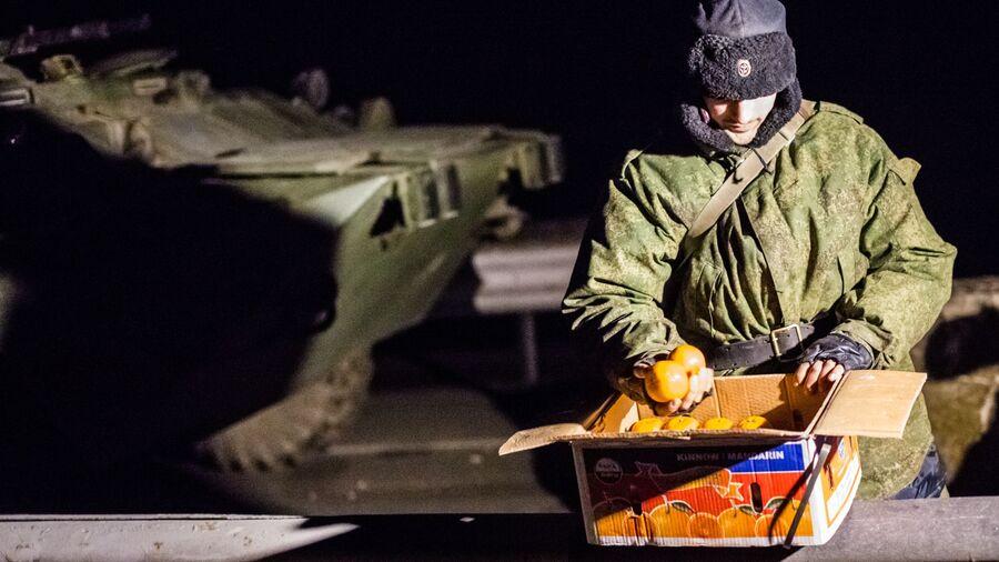 Военнослужащий с ящиком мандаринов на блокпосту на въезде в Крым в районе Армянска