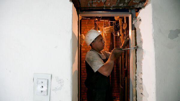 Специалист проводит замену лифтового оборудования в многоэтажном жилом доме