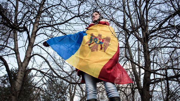 Участница акции протеста оппозиции в Кишиневе в национальном флаге Молдовы