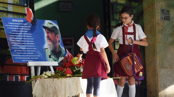 Дети возлагают цветы к портрету Фиделя Кастро у входа в школу в Гаване