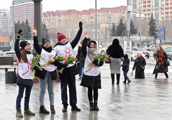 Волонтеры движения Мосволонтер, поздравляющие женщин с Международным женским днем в рамках добровольческой акции Вам, любимые!, у входа в Парк Горького в Москве