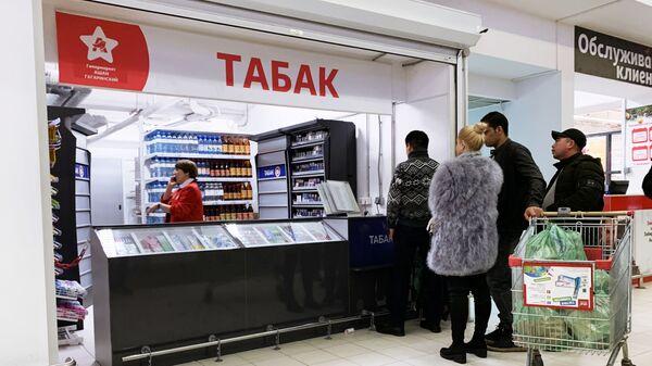 Покупатели стоят у табачной лавки