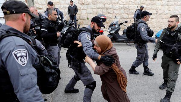 Израильский полицейский оттесняет палестинскую женщину