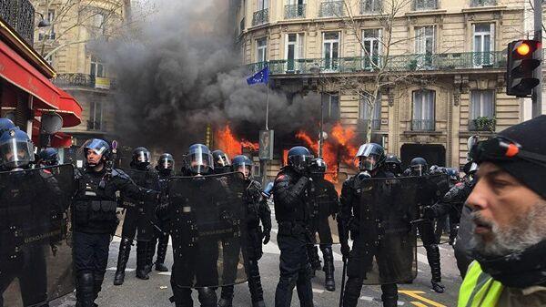 Полиция перед горящим зданием в Париже во время акции протеста желтых жилетов. 16 марта 2019
