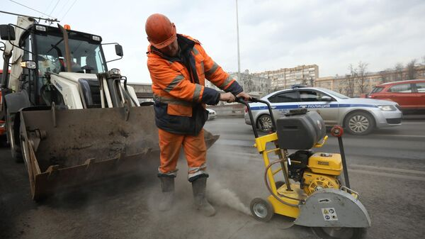 Рабочий бригады ГБУ Автомобильные дороги проводит латочный ремонт дорожного покрытия в Москве