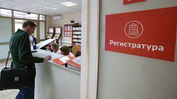 Посетитель у регистрационного стола в поликлинике
