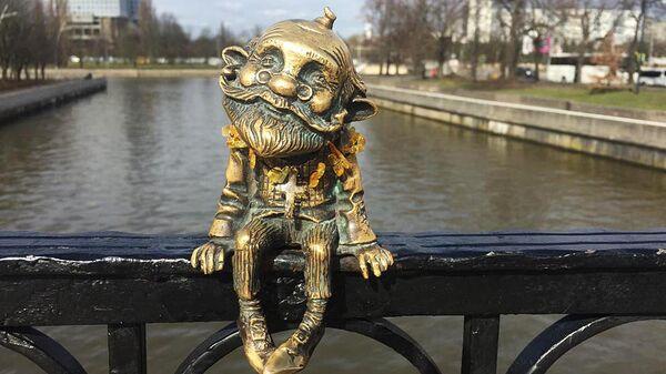 Фигурка домового-хомлина с янтарным крестиком на Медовом мосту в Калининграде