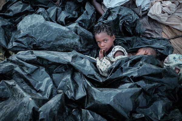 Дети прячутся от дождя под пластиковыми пакетами для мусора в Бузи, Мозамбик