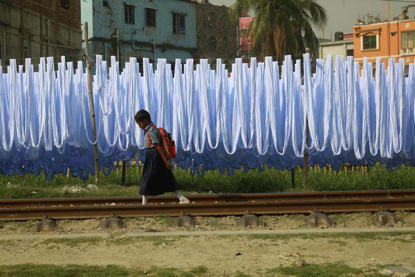 Девочка идет по железнодорожным путям в городе Нараянгандж, Бангладеш