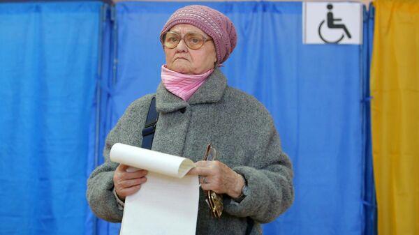 Пожилая женщина во время голосования на выборах президента Украины на одном из избирательных участков Киева. 31 марта 2019