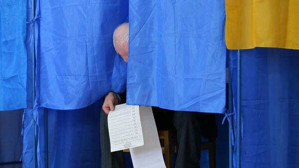 Мужчина изучает бюллетень на президентских выборах на одном из избирательных участков Киева