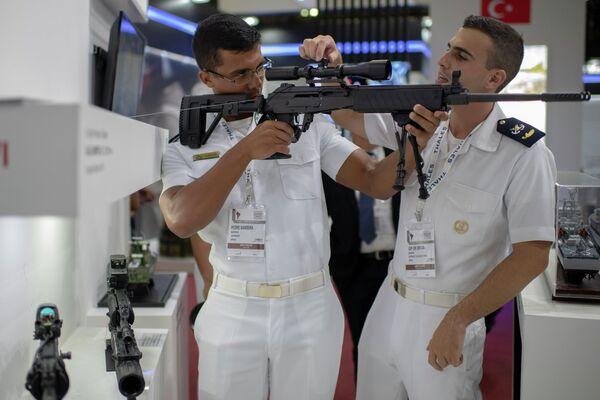 Военнослужащие ВМФ Бразилии осматривают прицел огнестрельного оружия на выставке LAAD Defense & Security 2019 в Рио-де-Жанейро