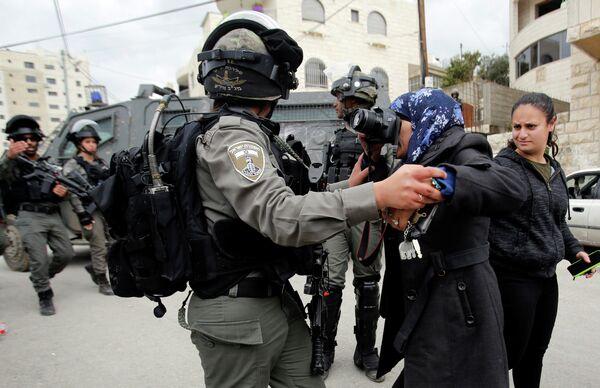 Израильский пограничник не дает фотографу сделать снимок палестинского дома в Бейт-Джале