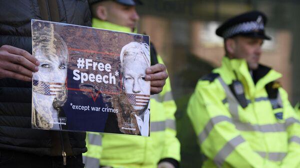 Мужчина стоит с плакатом в поддержку основателя WikiLeaks Джулиана Ассанжа у Вестминстерского суда в Лондоне