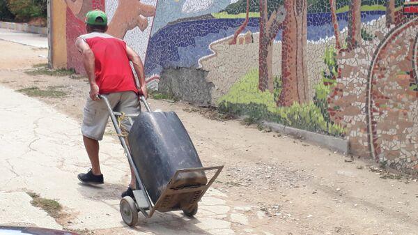 Житель района Катия Каракаса везет добытую воду из-за отсутствия водоснабжения в районе
