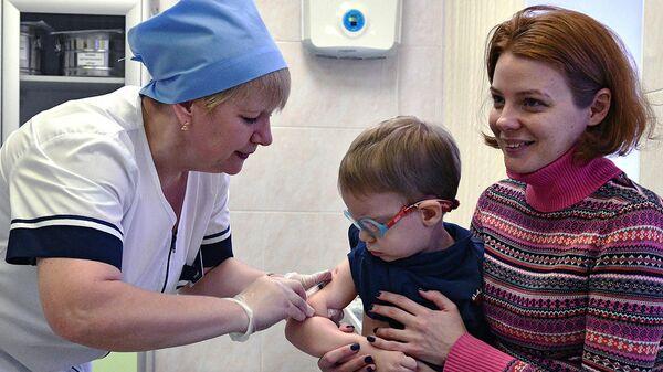 Медицинская сестра делает прививку от кори ребенку в детской поликлинике