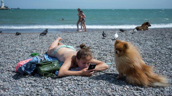 Девушка с собакой на городском пляже ялтинской набережной им. Ленина